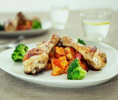 Mumsig varmrätt med vitlökskryddade kycklingben och en elegant potatis- och tomatblandning. Ett gott tillbehör till kycklingbenen är broccoli och en bit färskt bröd.