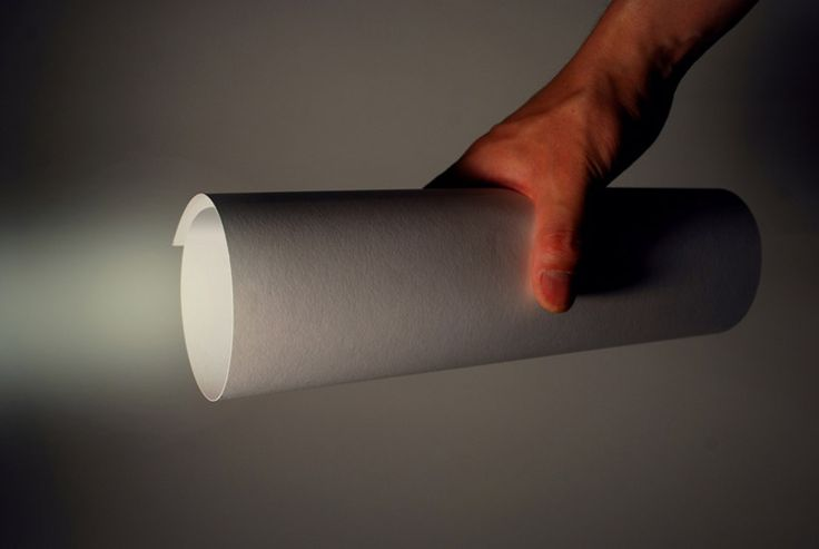 paper LED torch light by kazuhiro yamanaka. made exclusively using a cut-out piece of paper and a battery operated LED, the minimal torch light by japanese designer kazuhiro yamanaka rolls up to create an ample illumination source. when a user gyrates the sheet into a cylindrical form, the slit contained within the parchment extrudes inwards, automatically powering the LED attachment via two thin hidden switches.