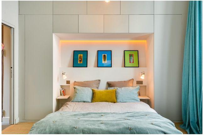 gain de place assuré grâce à cette disposition du lit en alcôve au milieu de placards sans poignées. la tête de lit est égayée par un trio d'encadrement de masques africains sur fond de couleurs vives et harmonieuses