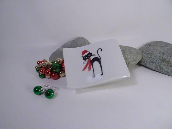 Voilà une jolie boite décorée dun petit chat couvert dun bonnet de père Noel,et son écharpe rouge il est tout prêt à célébrer Noël elle est en porcelaine ,décorée à la main rectangulaire,en forme de vague, A lintérieur de la boite ce petit chat coquin a laissé ses empreintes Idéale pour présenter un petit bijou ou pour ranger ses petites dents! Dimensions de la boite:longueur 8 cm, largeur 5,5 cm ,hauteur 2.5 cm Les couleurs sont fixées dans un four professionnel à 920 degrés,les décors sont…