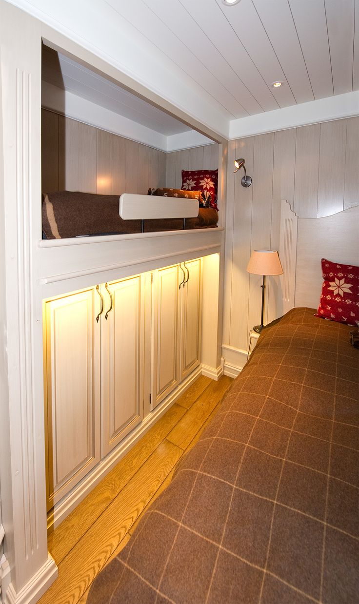 Smart use of space in a small bedroom. Bed with cupboards below left, and regular bed to the right. Hand-crafted and hand-painted by Os Trekultur.
