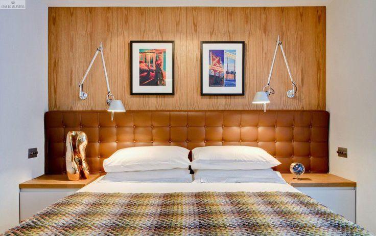 Cabeceira de couro com capitonê + painel de madeira com veios na vertical + luminárias Tolomeu de parede.
