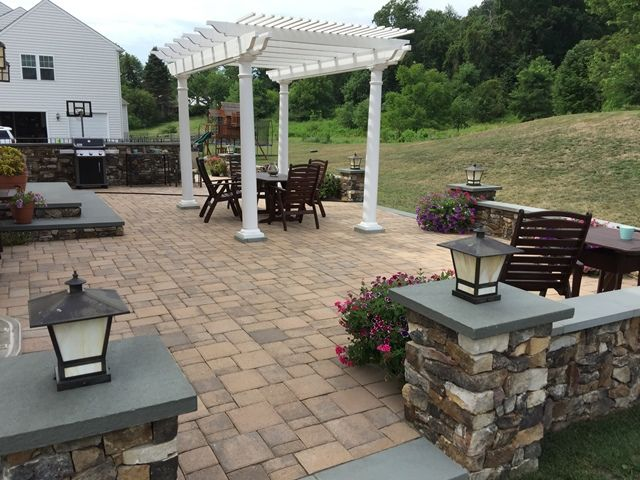 A Beautiful Paver Patio With Stone Seating Walls, Pillars, Lighting, And A  Pergola