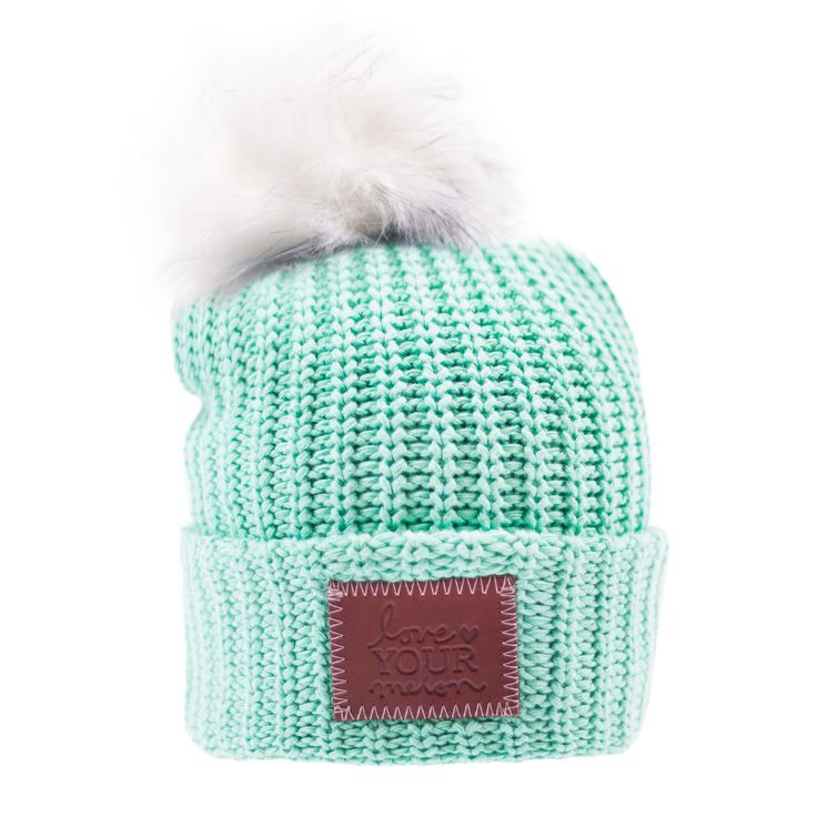 This pom beanie is knit out of 100% cotton yarn in a mint color. It features a brown leather patch that is debossed with the Love Your Melon logo and a detachable, white faux fur pom. Made in the USA,