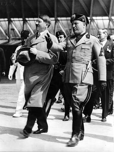 Adolf Hitler, who only recently assumed power over the German Reich, makes formal introductions with the leader of the Reich's southern neighbor of Italy, Benito Mussolini, during a diplomatic rendezvous in the Italian city of Venice. Hitler was furious throughout the entire 3 days of his visit due to his advisers suggesting he wear civilian clothes instead of his normal NSDAP attire, only to discover Mussolini and his entire Italian contingent were decked out in party uniforms.