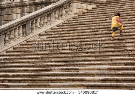Child running up the stairs of Cathedral of Girona, Catalonia, Spain. ascending, catalonia, child, church, conceptual, family, fighting, geometry, girona, marina, medieval, overcoming, power, religion, running, spain, stairs, stone, strenght, vacation, yellow, young, youth