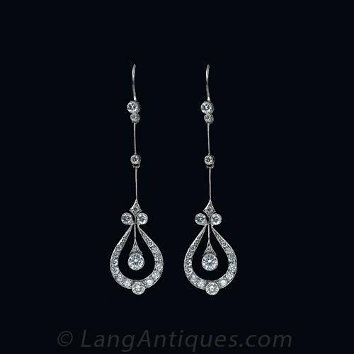 Graceful and gorgeous, these delicate drops perfectly represent the femininity inherent in Edwardian jewelry design. A stylized, diamond set tear drop shape frames a freely swinging bezel set diamond all of which are suspended from an extremely thin and elongated milgrained knife edge wire. These earrings measure 2 inches in length from the top of the ear wire to the bottom. These earrings are contemporary and made in the Edwardian style.