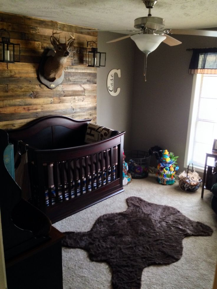Hunting lodge nursery with pallet wall, deer mount, bear rug, and lanterns.