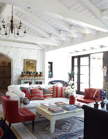 """Living Room. """"This isn't a very feminine house, but women love it,"""" McDowell says. She painted all the walls and ceilings the starkest white she could find: a Benjamin Moore primer, Super Spec Flat. Pillows on the living room sofa are by Laurel Adams Design; papier-mâché bulldogs, Animal Art Antiques."""