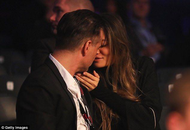Ringside smooch: Colin Farrell and his mystery girlfriend packed on the PDA on Saturday evening in ringside seats at Anthony Joshua's boxing match in Cardiff, Wales