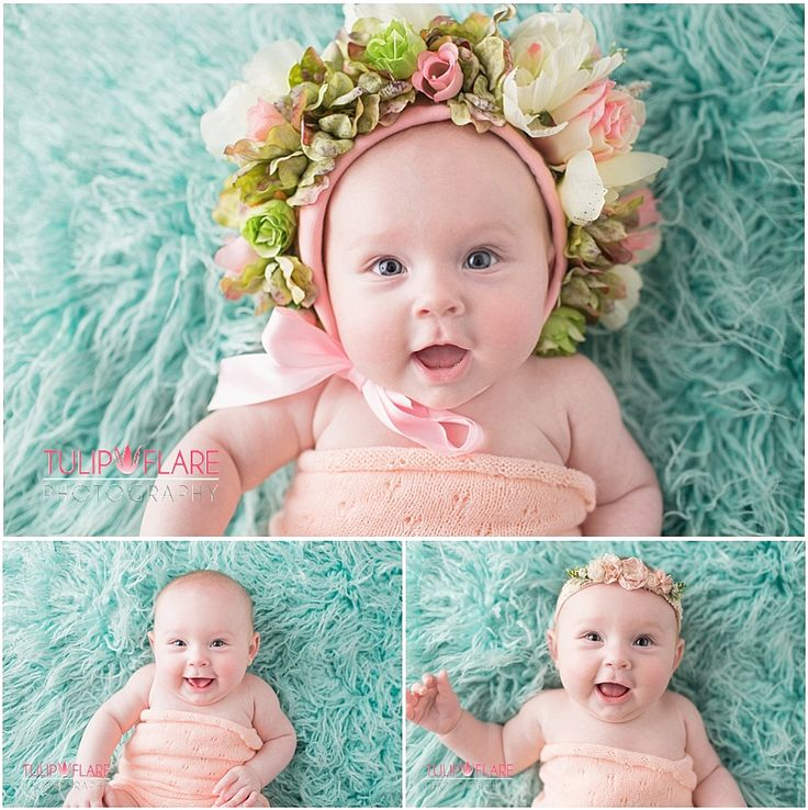 Baby on a green rug with a flower bonnet