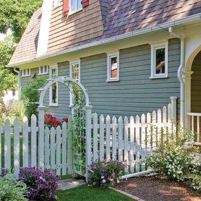 A gated garden arch and picket fence is surrounded by old-fashioned hydrangeas, dogwoods, roses, and lilacs. | Photo: Judith Bromley | thisoldhouse.com