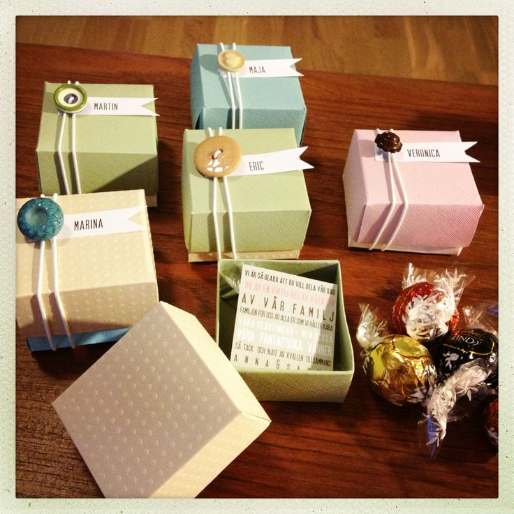 Seating cards. Handmade paper boxes with a name tag on top and chocolate inside. Sealed with an elastic ribbon and a cute button.