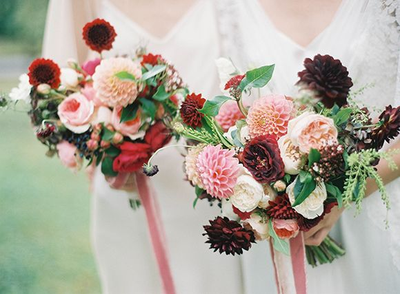 The bridesmaids will carry bouquets of pink garden roses, blush spray roses, blush astilbe, burgundy scabiosa, red ranunculus, and hints of seasonal greenery in navy ribbon with the stems showing.