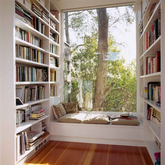 What a dream to have a reading nook like this: floor-to-ceiling bookshelves ending in a huge window overlooking tall trees.