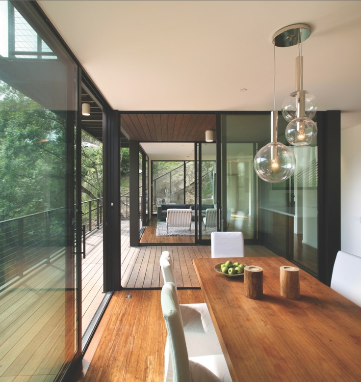 Several sliding glass doors open this house to create true indoor-outdoor living. Dining room, patio, balcony, pendant lights, wood floors, dining table, modern, contemporary, http://www.westernwindowsystems.com