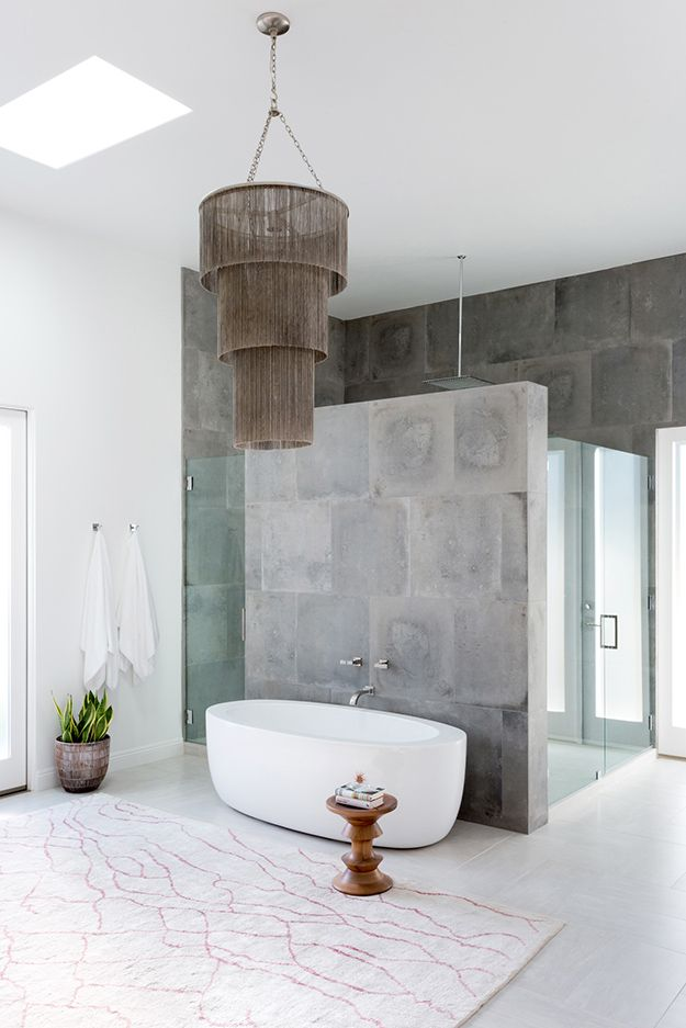 The master bathroom is done with grey stone, there\'s a glass shower ...