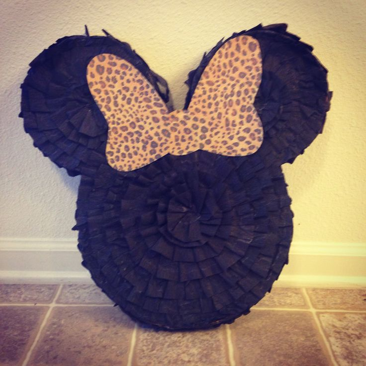 DIY Minnie Mouse piñata made from cardboard (diaper box), tape, crepe paper & glue. First cut out 2 Mickey Mouse heads the same size. Next cut 1-2 inch strips of cardboard. Rub the strip against the edge of a hard surface like a table to loosen them up. Tape the strips along the edge of one Mickey head then place the second Mickey head on the strips & tape. Leave the space between the ears open to fill the piñata. Click on the source for the tutorial I followed & more detailed instructions