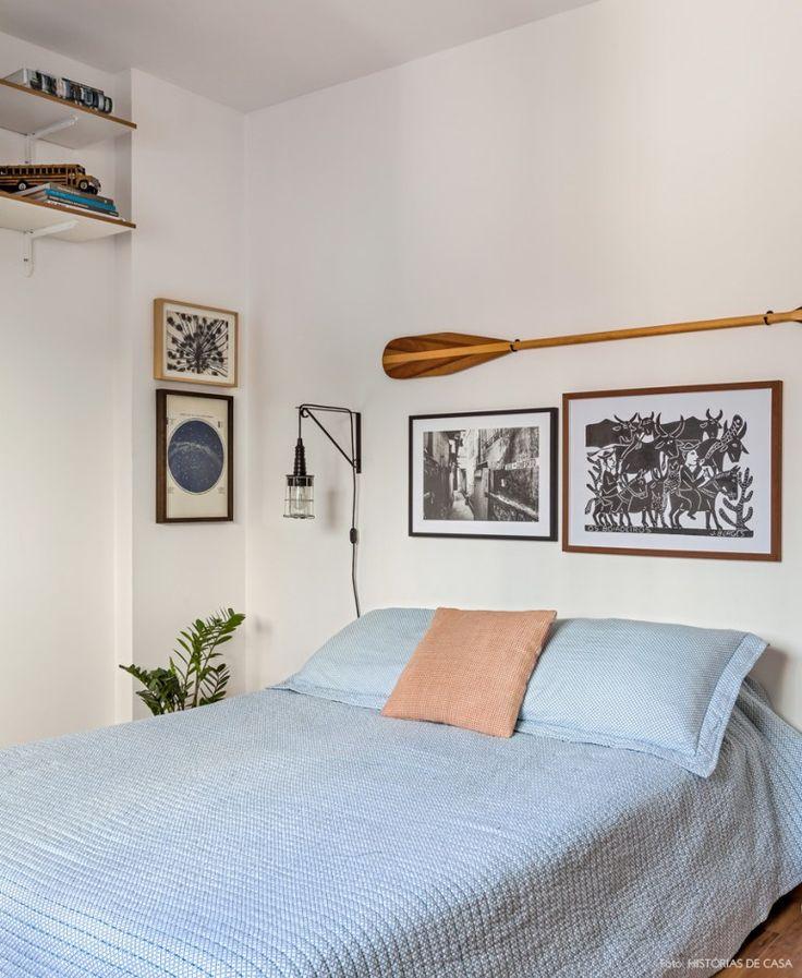 Quarto de casal tem quadros e remo de madeira emoldurando a cabeceira.