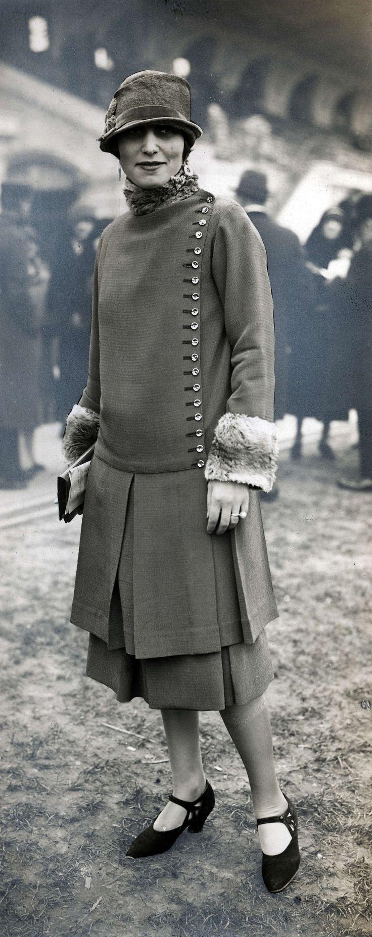 Damesmode. Pak met jas en rok in dezelfde stof. De jas heeft links een lange rij knopen en de manchetten zijn met bont afgezet. De  onderkant van de mantel en rok zijn geplooid. Het model draagt daarbij een hoedje tot net boven de ogen. Zonder plaats, 1926.