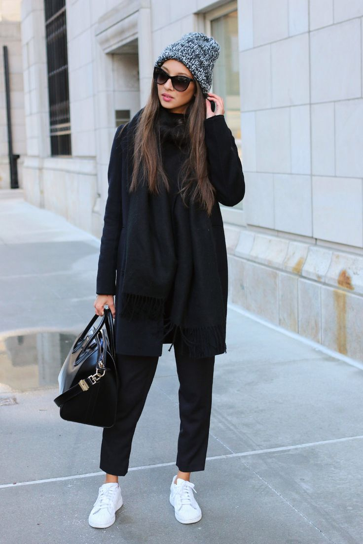 This combination of a black coat and black trousers is perfect for off-duty occasions. A pair of white leather low top sneakers brings the dressed-down touch to the ensemble.   Shop this look on Lookastic: https://lookastic.com/women/looks/coat-chinos-low-top-sneakers/15685   — Grey Knit Beanie  — Black Scarf  — Black Coat  — Black Leather Tote Bag  — Black Chinos  — White Leather Low Top Sneakers