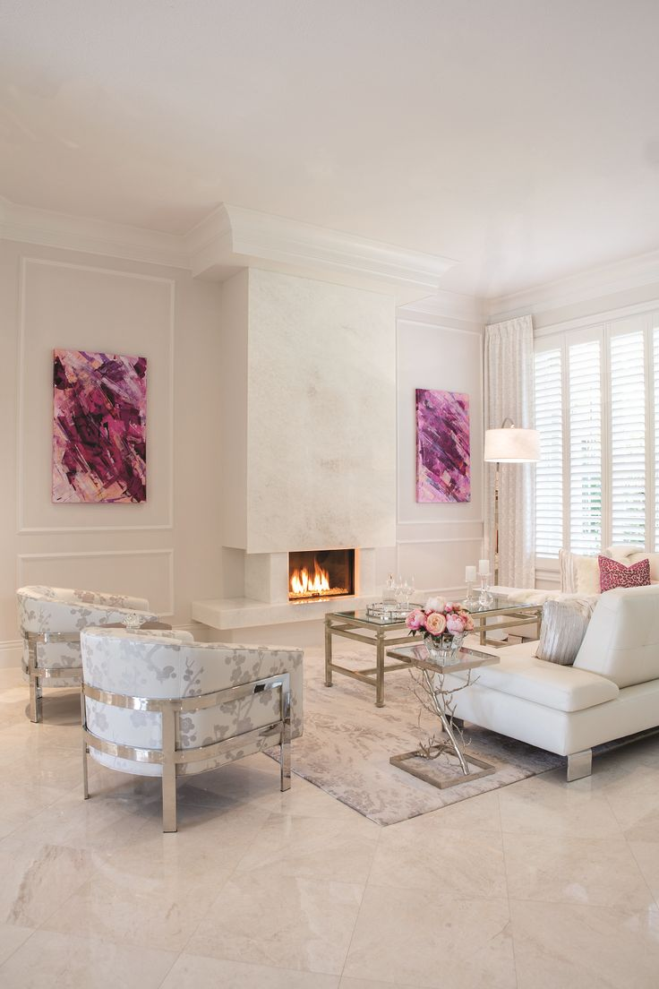This living room delivers a striking aesthetic with light gray-painted walls, white marble floor tiling and a matching marble fireplace. Two abstract paintings add vibrant pops of purple and pink, while a large mirror with a chrome frame custom-ordered from Italy hangs to their left. In addition to the large, white sectional are two conversation chairs with gray floral motifs and chrome-finished bases. Interior design by Ingrid de Villiers, Robb & Stucky
