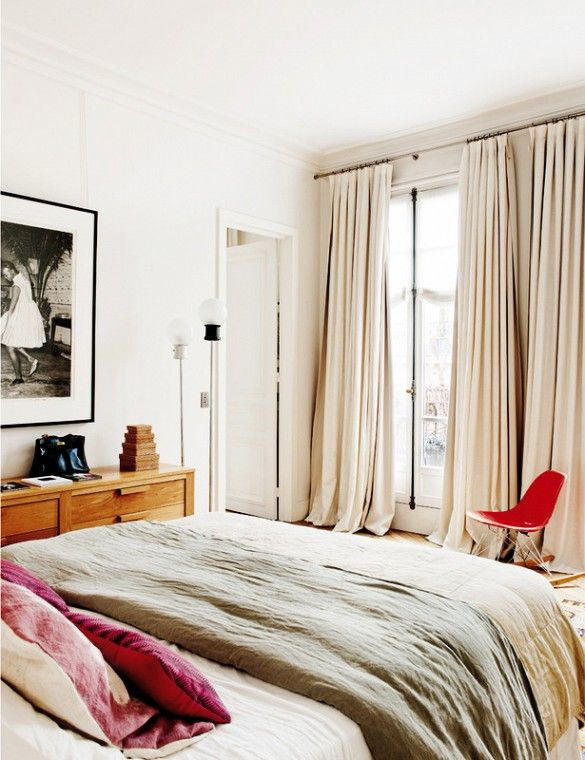 Modern bedroom with linen bedding, long curtains, and framed photography print.