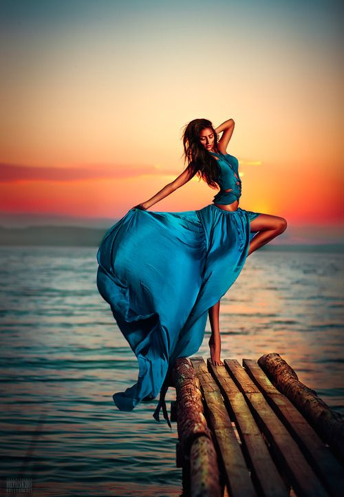Awesome picture! Blue long dress in petrol on a landing stage with a Sunset!