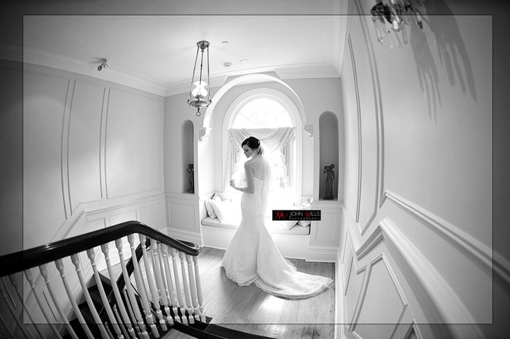 Black and White Bride waiting in staircase Slide show of this wedding HERE http://www.weddingsbyjohnwills.com/weddings-at-paletta-mansion-in-burlington/