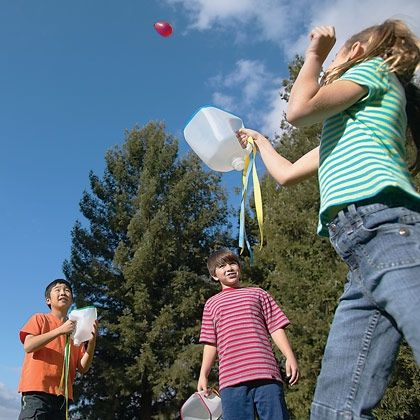 Water Balloon Catch    Create the catchers by cutting the bottom off a gallon-size milk jug (one for each player), taping the cut edges, and decorating with ribbon, as shown.    Fill a bunch of water balloons to the size of a grapefruit.    See how many times you can toss the balloons without breaking them or how far you can catch and throw them.