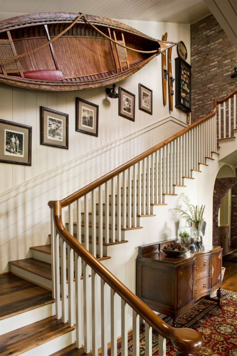 Sweeping cabin staircase accented with family heirloom photos and a mounted wooden boat.