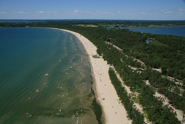 """Sandbanks Provincial Park is located two and half hours east of Toronto and south of Belleville.  Giant sand dunes and golden beaches form two of the largest freshwater baymouth sandbars in the world here, on the shores of Lake Ontario. Efforts to stabilize shifting sands disturbed by farming have revived distinctive dune plants such as bluets, butterfly weed and sand spurge. Trails feature dune stairs to protect this delicate vegetation."""