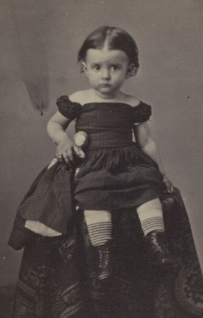 Antique photo of little girl in an off-the-shoulder dress with her doll, circa 1860.