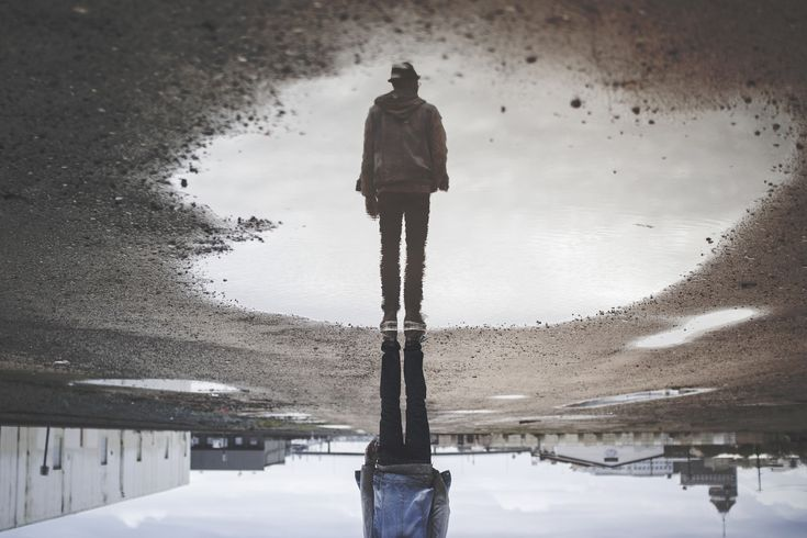 A puddle reflection of a sad guy.