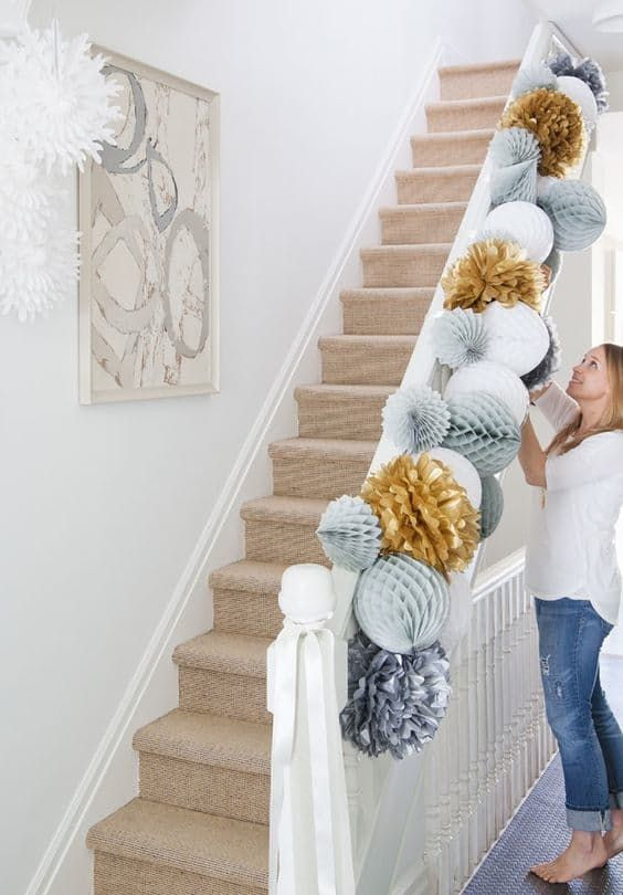 The stair banister is a traditional place for decorations. Instead of trailing greenery, go for these huge paper pom poms, festive in a slightly quirky way. As seen at House & Home. //  Over-the-Top Decorating Ideas for the Hardcore Holiday Enthusiast — Minimalist/Maximalist