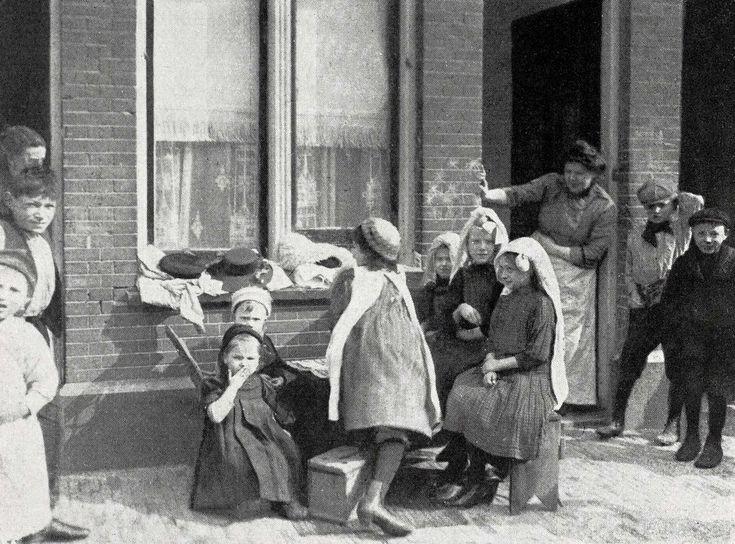 Kinderen spelen op de Baangracht in de Amsterdamse buurt De Jordaan. Een moeder kijkt vanuit de deuropening toe. Op de muur staan krijttekens. Nederland, datum onbekend [omstreeks 1910]