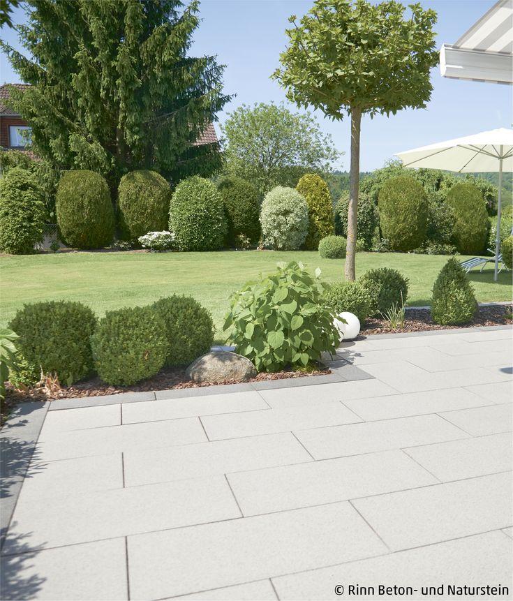 Eine Terrasse mit Blick ins Grüne. Die Rasenfläche wird abgegrenzt von einem kleinen Beet, hier finden sich auch wieder runde Formen und Sträucher,…