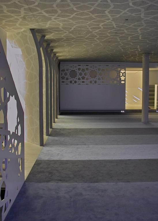 Carved concrete slabs along the side of the prayer room.  Abstract star motifs bearing the 99 Names of God in calligraphy, designed jointly by the artists Lutzenberger + Lutzenberger from Bad Wörishofen and Mohammed Mandi from Abu Dhabi.  Islamic Forum of Penzberg, Germany.  Built in 2005 and designed by Alen Jasarevic.