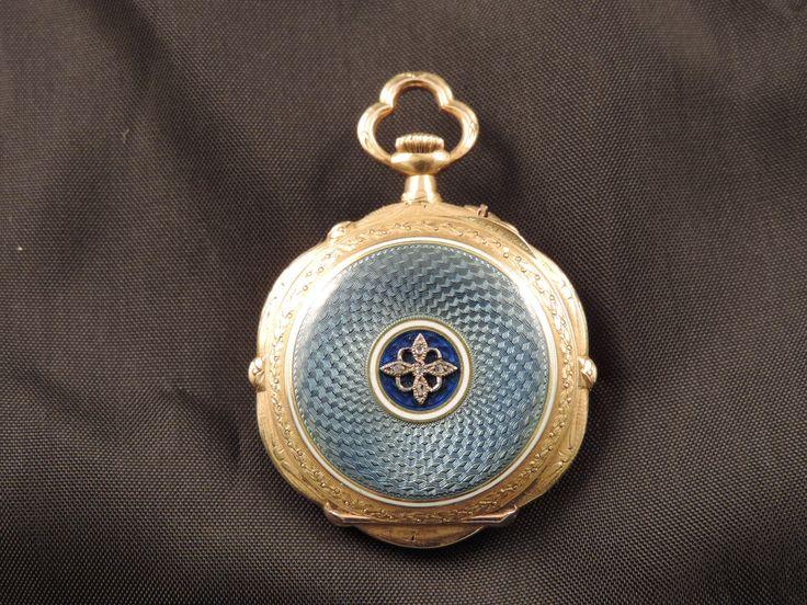 Orologio da collo per signora Belle Epoque (1871-1914) realizzato in oro giallo 18 carati, decorato con smalto bianco, smalto azzurro guilloché e 5 punti di diamanti naturali, taglio rosetta. Il quadrante è in metallo satinato con numeri arabi in smalto nero, come le lancette. A carica manuale, funzionante e in ottime condizioni, è firmato Louis Rey, Marseille. In vendita su www.mirabilia.gallery per 1.140,00 € (IVA inclusa).