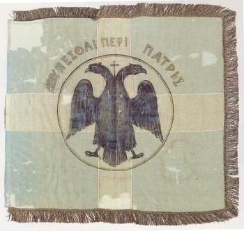 181) Σημαία από το Μακεδονικό Αγώνα. Κυανόλευκη, φέρει δικέφαλο αετό και την επιγραφή ΑΜΥΝΕΣΘΑΙ ΠΕΡΙ ΠΑΤΡΗΣ.