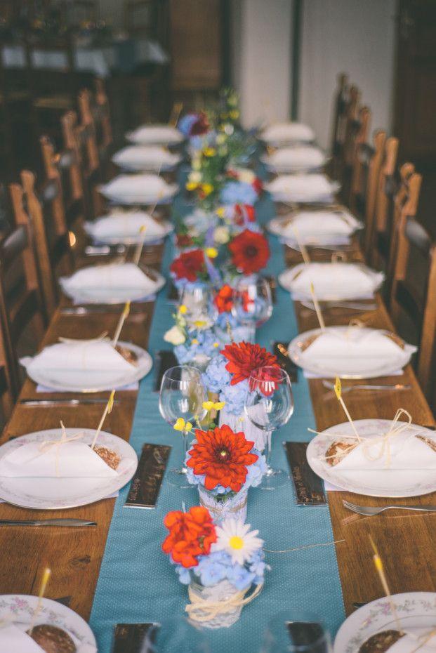 longue table avec petits pots de fleurs et panneaux rando pour name cards