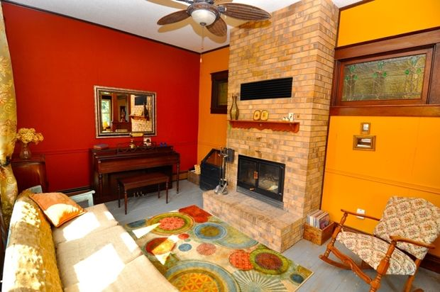 Red Orange Living Room Color Area rug Ceiling fan Chair rail Crown molding Eclectic End table Painted hardwood floor Rocking chair Sofa Stained glass window Wood bench Wood crown molding