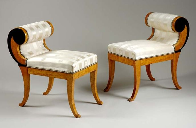 Pair of Biedermeier Ebonized and Birch Window Benches Second quarter of the 19th century Each rectangular padded seat with a single scroll arm rest, raised on sabre legs.