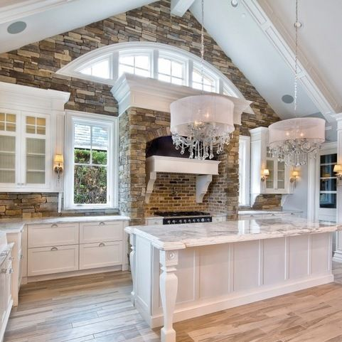 Shingle Style white kitchen with cathedral ceiling, arched clerestory windows, and stone accents.