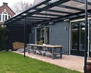 Mirjam Nouwens spray painted the outdoor dining table at her home in the Netherlands the same color as the exterior wall. A patio cover allows her and her two sons to enjoy their backyard throughout the seasons.