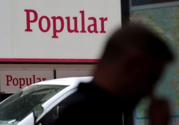 © Reuters. People walk past a branch of Spain's Banco Popular in Madrid, Spain