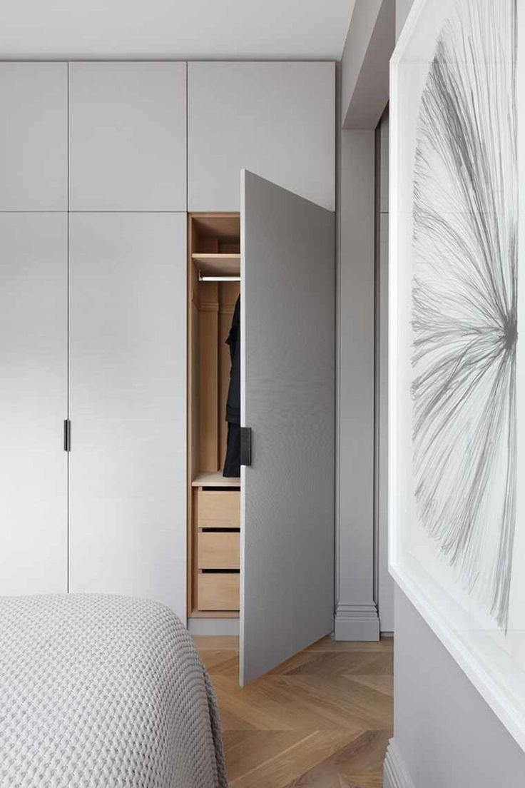 Fabric-clad wardrobe doors custom designed by INTERIOR-iD, along with Joseph Giles leather pulls, add texture to the master bedroom.