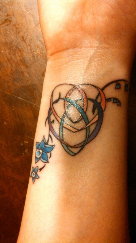My Motherhood knot tattoo with the blue flower represents my daughters birthstone color. The Celtic Knot of Motherhood is unassuming stylized holy trinity knot depicting a parent and child embrace. Combined with a Celtic trinity knot it is a true statement to the enduring bond between a Mother, her child, and her faith. The Celtic motherhood symbol looks like 2 hearts made out of knot work. One heart is lower than the first heart and both hearts are intertwined in a continuous knot.  It has…