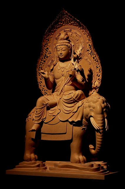 仏像彫刻原田謹刻 普賢菩薩像(ふげんぼさつぞう) 【普賢菩薩】 梵名サマンタ・バドラ。「普く賢い者」の意味であり、彼が世界にあまねく現れ仏の慈悲と理知を顕して人々を救う賢者である事を意味する。理知・慈悲をつかさどり、また延命の徳を備える。智慧を司る文殊菩薩と並んで釈迦仏の二脇侍として知られる。文殊菩薩が悟りの知性的側面を象徴しているのに対し、普賢菩薩はその実践的側面(普賢行)を象徴する。六牙の白象に乗った姿で表現される。辰年・巳年の守り本尊である。