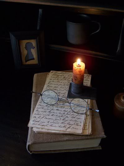.Love the silhouette in the background with the candle and old glasses on top of the book-great vignette.